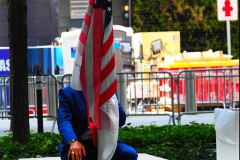 Germano Rvieira sits with the flag of honor near the north reflecting pool at the 9/11 Memorial on the 20th anniversary of the September 11 attacks in Manhattan, New York on September 11, 2021.