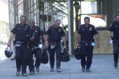 September 13, 2001--World Trade Center--Exhausted looking NYPD police officers from the 102nd Precinct in Queens walk with their helmets and gear to search for survicors in Lower Manhattan/ Ground Zero of the destroyed World Trade Center after terrorists attacked the site with thwo hijacked jetliners two days earlier on Tuesday September 11, 2001. (©2001 Kevin P. Coughlin/Independent Photojournalist)