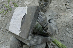 """September 13, 2001--World Trade Center--Double Check (1982), a statue by sculptor John Seward Johnson II, of a businessman checking his attaché case, is pictured with a note taped to the briefcase at Liberty Plaza Park, across from the World Trade Center on September 13, 2001.  The note reads: """"IN MEMORY OF THEOSE WHO HAD GAVE THEIR LIVES TO TRY AND SAVE SO MANY"""". (©2001 Kevin P. Coughlin/Independent Photojournalist)"""