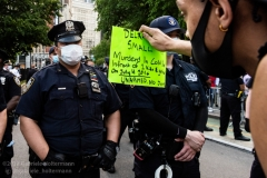 A protester tells an NYPD officer to look at his sign with the name of a man killed by police as demonstrators protest the death of George Floyd at the entrance to the Brooklyn Bridge blocking traffic on May 30, 2020, in New York City. (Photo by Gabriele Holtermann)