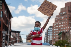 A young boy holds up a sign from a car while watching Black Lives Matter protesters pass by on May 30, 2020. (Photo by Gabriele Holtermann)