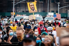 A protestor holds a painting of George Floyd demonstrators take to the streets protesting his death in Brooklyn, New York, on June 5, 2020. (Photo by Gabriele Holtermann)