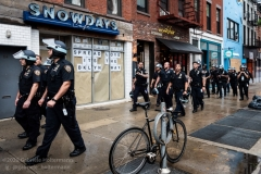 NYPD officers walk past a store as demonstrators take to the streets protesting the death of George Floyd in Brooklyn, New York, on June 5, 2020. (Photo by Gabriele Holtermann)