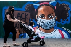 A young girl looks at the mural by artist Lexi Bella showing a young African-American woman wearing a face mask supporting black lives on June 15, 2020, in Brooklyn, New York.  (Photo by Gabriele Holtermann)