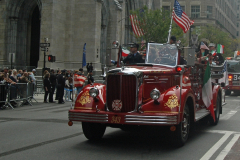 An antique Fire Department vehicle rolls up Fifth Avenue.  The license plate number commemorates the 343 firefighters who died on 9/11.