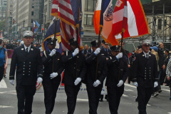 An honor guard from the Fire Department marches along the parade route.