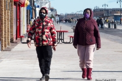 Coney Island Brooklyn. People stroll the Boardwalk in winter clothes on this sunny and cold day, 37 degrees some people sat on benches and others sunned 
