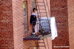 Out the Window  Woman hangs clothes on the Fire Escape to dry during the Covid 19 pandemic  8/9/2020