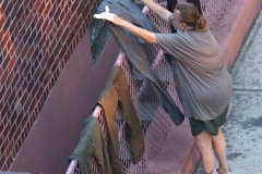 Covid19 Laundress: Woman hangs laundry on chain link fence leading to basement garage door during Covid Pandemic and heat wave   7/21/2020