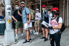 A group of people eating ice-cream look on as the Guardian Angels patrol the Upper West Side in New York City on August 9, 2020.  The neighborhood has experienced an uptick in crime and drugs after hotels have been turned into homeless shelters. (Photo by Gabriele Holtermann)