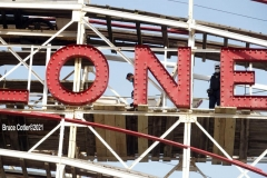 New York- Workers walk the tracks of the World Famous Coney Island Cyclone roller coaster in preparations for opening season. Last summer Coney Island was shut down because of the Covid Pandemic