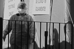 March 27, 2020: A Novel Coronavirus / COVID 19 testing center at Elmhurst Hospital Center in Queens, New York City. A medical care worker surveys the line of people wanting to be tested for COVID 19.