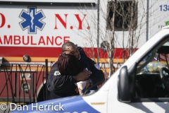 "April 1,  2020:  An EMT paramedic shouts out ""We need more hugs! It's just crazy here.""- after hugging his colleague and getting back into his ambulance. EMS workers and other first responders are on the frontline of the battle against COVID-19 or the novel coronavirus in addition to their regular workload."