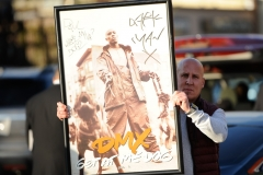 A fan of DMX holds a autographed poster during a funeral procession at Christian Cultural Center in the borough of Brooklyn, New York on Sunday, April 25th, 2021.