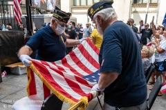 "Two war veterans fold the American flag at the ""Don't Give Up the Ship"" rally outside City Hall Park in New York City on August 22, 2020. The rally, led by Staten Island based artist Scott LoBaido, called out the Mayor's failure addressing the recent spike in gun violence and increase in homeless encampments. (Photo by Gabriele Holtermann)"