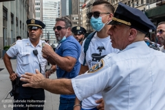 """NYPD officers diffuse a tense situation between Black Lives Matter protestors and Blue Lives Matter protestors after  the """"Don't Give Up the Ship"""" rally outside City Hall Park in New York City on August 22, 2020. The rally, led by Staten Island based artist Scott LoBaido, called out the Mayor's failure addressing the recent spike in gun violence and increase in homeless encampments. (Photo by Gabriele Holtermann)"""