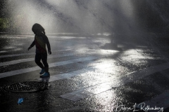 Adults and kids cool off in the traditional city life way, via am open fire hydrant, on a hot summer day on the Upper West Side Of New York City on 23 August 2020