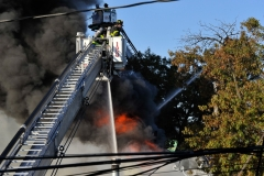Firefighters operate as heavy fire vents through the roof of a one story building. (Photo by Lloyd Mitchell)