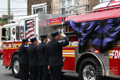 """Monday, August 30, 2021 FDNY Line Of Duty Funeral Staten Island, NY Photographs by Mary DiBiase Blaich   Firefighter Stephen J Reilly was remembered today with a Funeral Mass at Sacred Heart Church in Staten Island.  He died of cancer related to his 9/11 service. After the funeral Mass, family members were presented with FDNY items, including his helmet. Attending were his company, Engine 155, Fire Commissioner Daniel Nigro, and many firefighters, family, and friends.  During the funeral, a call came in for a high angle rescue of a worker, and some of the mourners who were on duty left with lights and sirens.  One firefighter holds his handy talkie to listen to the """"run"""". While another looks down the street to view responding tower ladder #79."""