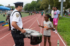 A member of the NYPD marching band interacts with a young person at the inaugural flag football tournament in memory of Det. Keith Williams. (Photo by Gabriele Holtermann)