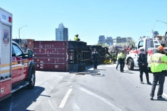 Cops, firefighters and big rig towers work to secure a tractor trailer that flipped over and sent 100's of gallons spilling onto the Brooklyn- Queens Expressway at Flushing Avenue.