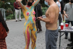 Andy Golub founder and Executive Director of Human Connection Arts paints two models near the Washington Square Arch in New York's Greenwich Village neighborhood.