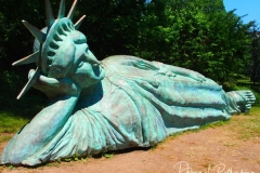 """Artist Zaq Landsberg's sculpture entitled """"Reclining Liberty"""" inside Morningside Park in New York City .The sculpture was created by Landsberg and features the Statue of Liberty posed on her side with her head propped up by her hand. The 25 foot long sculpture  is covered in oxidized copper paint and features a steel crown and was created using wood, foam and plaster resin."""
