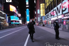 A Police Officer takes a selfie in a mostly empty Times Square in New York City that remains empty due to Covid-19 restrictions.
