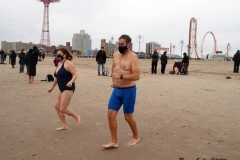 Coney Island New York: January 1 , 2021. In years past, the Coney Island Polar Bear Club would hold their annual New Year's Plunge; however, due to the Coronavirus this year, the event was canceled. In spite of this, New Year's revelers decided to hold their own non-sanctioned plunge at the beach.