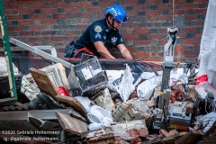An NYPD police officer carefully wraps the body of the construction worker, who died in a scaffolding accident, into tarp at 136 E 36th Street in New York City on July 16, 2020. The accident also injured three co-workers. (Photo by Gabriele Holtermann/Sipa USA)