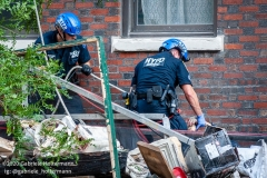 Two NYPD police officers carefully wrap the body of the construction worker, who died in a scaffolding accident, into tarp at 136 E 36th Street in New York City on July 16, 2020. The accident also injured three co-workers. (Photo by Gabriele Holtermann/Sipa USA)