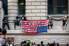 Occupy City Hall protesters hold up an American flag during a rally in New York City on June 23, 2020. The demonstrators demand defunding the NYPD by $1 billion and invest in education instead. (Photo by Gabriele Holtermann)