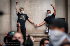 Two Occupy City Hall protesters hold hands during a rally in New York City on June 30, 2020. Protesters demand that the New York City Council cut the NYPD budget by at least $1 billion.  (Photo by Gabriele Holtermann)