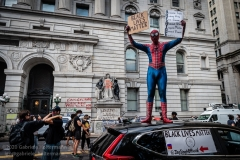 A man dressed as Spiderman holds up signs during an Occupy City Hall rally in New York City on June 30, 2020. Protesters demand that the New York City Council cut the NYPD budget by at least $1 billion.  (Photo by Gabriele Holtermann)