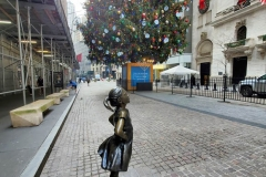 December 13,2020  Wall Street in front of the New York Stock Exchange residents and tourists visit the Fearless Girl statue and take photographs by the Stock exchange Christmas tree.