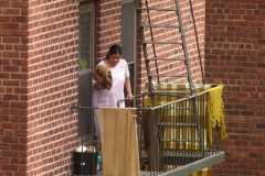 New York-  Tenant climbs out the window from her apartment  to  put out wet wash to dry on the fire escape of her Brooklyn building.