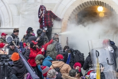 Washington, DC - January 6, 2021: Rioters use tear gas while clash with police trying to enter Capitol building through the front doors