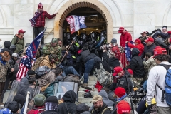 Washington, DC - January 6, 2021: Rioters clash with police trying to enter Capitol building through the front doors