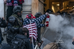 Washington, DC - January 6, 2021: Pro-Trump protester uses tear gas against police during rally around at Capitol building when they tried to break in through front doors