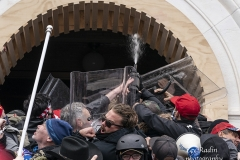 Washington, DC - January 6, 2021: Pro-Trump protesters seen using tear gas against police as they try to enter Capitol building through front doors