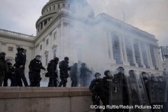 After supporters stormed the building earlier, police are caught in a haze after smoke canisters and chemical irritants were dispatched by police on the steps of the United States Capitol in Washington, D.C., Wednesday, Jan. 6, 2020, as they protest the electoral college certification of President-Elect Joe Biden.