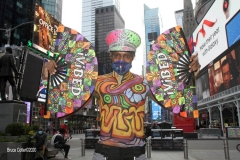"""New York City. """"The Crossroads of the World""""  Times Square. Andy Golub Artist/Founder of Human Connection Arts paints 3 models in Times square, as onlookers watch and street performers and costume characters entertain vistors."""