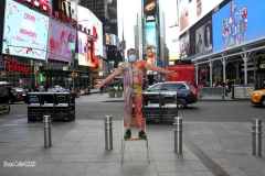 """New York City. """"The Crossroads of the World"""" Times Square. Andy Golub Artist/Founder of Human Connection Arts paints 3 models in Times square, as onlookers watch and street performers and costume characters entertainvistors."""
