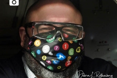 An MTA Conductor in New York City on Christmas Eve wears a mask showing all the various subway lines.
